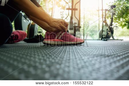 Woman tying shoelaces at gym vintage tone still life.