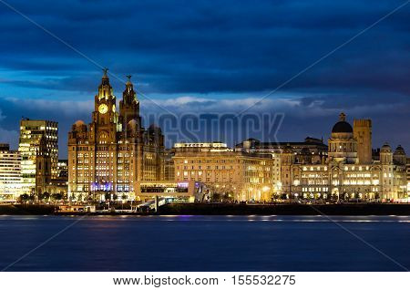 The world famous Liverpool skyline by night taken from Wirral across the River Mersey on a long exposure.