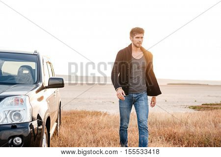 Serious young casual man walking near his car at the seaside