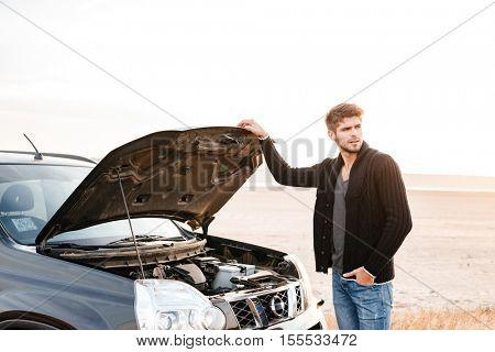 Young upset casual man standing at his broken car outdoors
