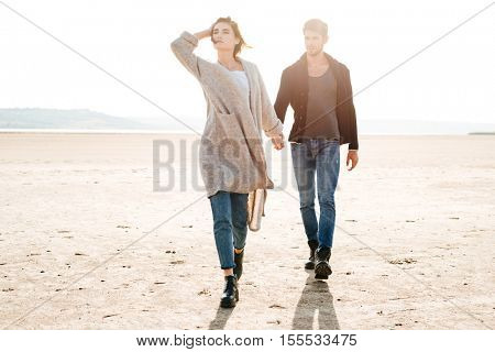 Portrait of a romantic young couple walking on the seaside in autumn