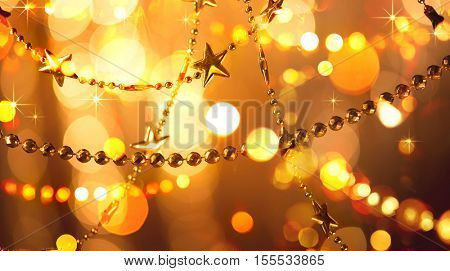 Christmas and New Year glowing Background with Holiday Decoration garland, tinsel and stars. Abstract Blurred Bokeh Holiday Backgdrop. Blinking Garland. Christmas Tree Lights Twinkling