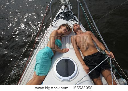 Man and woman lie on snout of yacht on river at summer sunny day, top view