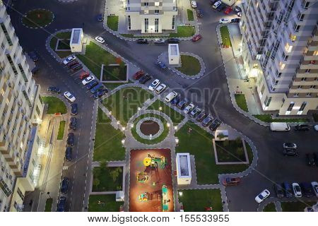 Parking, common area on stylobate in residential complex at summer evening, top view
