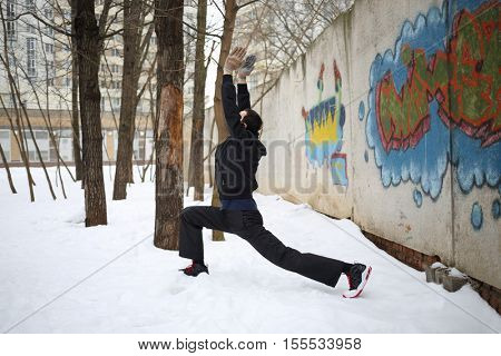 Man does exercises next to concrete wall with graffiti at winter