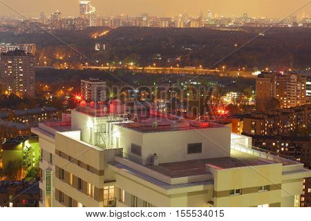 Roof of tall building with signal lights and night panorama of Moscow, Russia