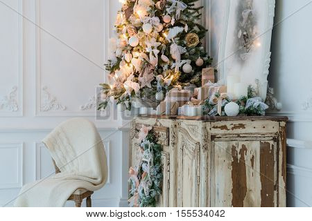 Christmas decoration on ancient vintage old commode chest of drawers. Hand made craft gifts, candels and a tree at background. Selective focus.