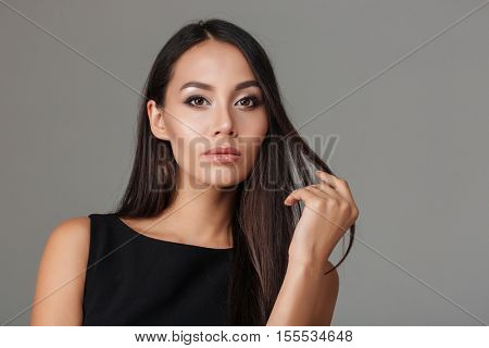 Close up portrait of a sensual young brunette in black dress looking at camera isolated on a gray background