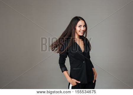 Smiling lovely woman in black suit standing and looking at camera over gray background