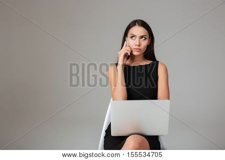 Displeased young brunette woman sitting with laptop and talking on mobile phone over gray background