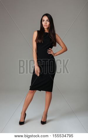 Full length portrait of a serious trendy woman in black dress standing isolated on a gray background