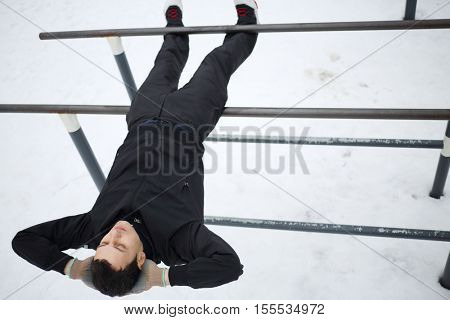 Man does exercises on parallel bars on sport playground in yard at winter