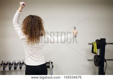 Woman does exercises with small dumbbells in gym with fitness equipment, back view