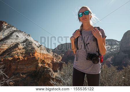 Young woman tourist with camera standing in the Zion National Park, USA