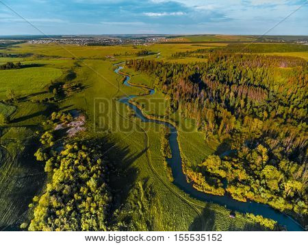 Aerial view of green meadow and small river