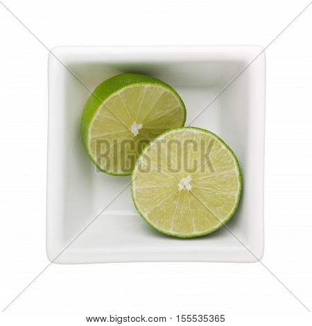 Lime fruit in a square bowl isolated on white background