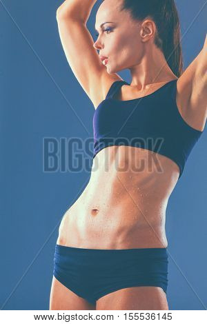 Muscular young woman standing on gray background