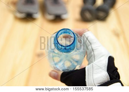 Bottle of water in hands close-up, cropped view, foreground, Sneakers and dumbbells on a wooden background, sport and Fitness, drinking from the bottle