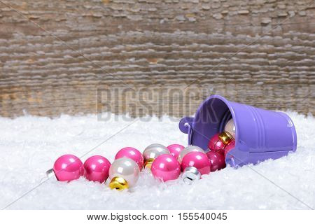 The bucket with scattered Christmas balls on snow with wooden background