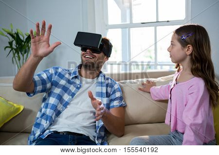 Father using virtual reality headset while daughter sitting beside him in the living room at home