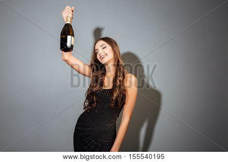 Model with bottle. holding bottle in hand. in black dress