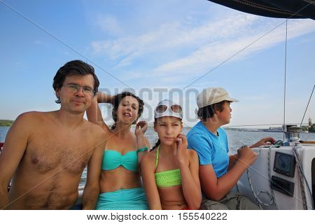 Mother, father, daughter and son sail on yacht on river at summer day