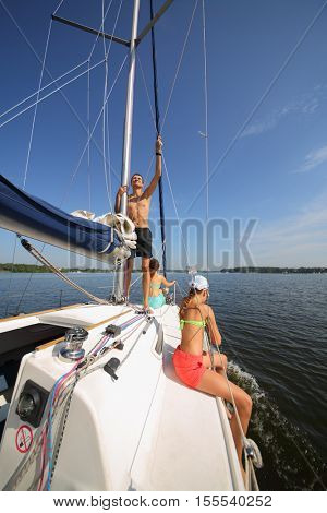 Happy father, mother and daughter sail on yacht on river at summer day