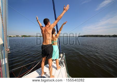 Man and woman pose as birds on snout of yacht on river at summer day, back view