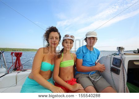 Happy mother, daughter and son sail on yacht on river at summer day