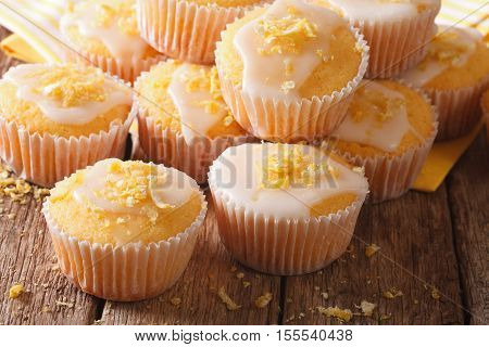 Lemon Muffins With Icing Sprinkled With Zest Close-up. Horizontal