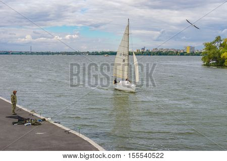 DNEPR UKRAINE - SEPTEMBER 24 2016:Scenery with lonely fisherman sailboat and flying gull on a Dnepr river embankment in center of Dnepr city at autumnal weekend at September 24,2016