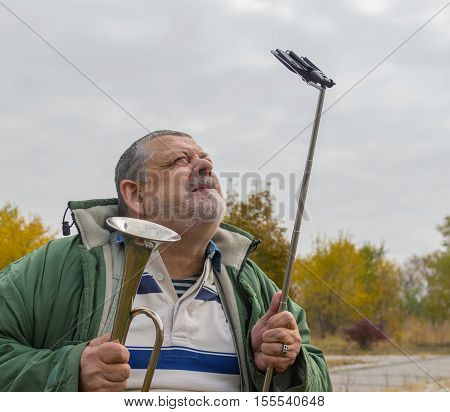 Portrait of ridiculous senior man making faces while doing selfie outdoor
