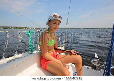 Girl in white cap is on yacht during sailing on river at sunny summer day