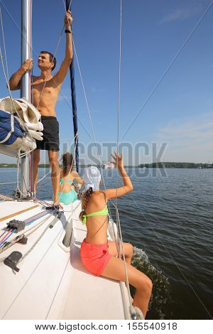 Father, mother and daughter sail on yacht on rive at summer, child waves hand for big ship