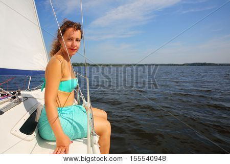 Pretty woman sits on yacht during sailing on river at sunny summer day