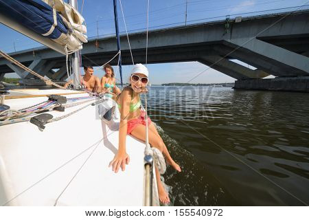 Father, mother and daughter sail on yacht on river near bridge at summer, focus on child