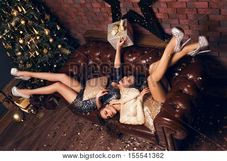 Two  Girls Lie On The Bed In Beautiful Dress And Smiling After Christmas Party With Presents And Lau