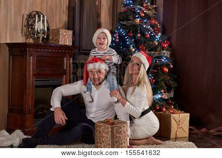 Happy family with  gifts sitting near Christmas tree at home. Merry Christmas and Happy New Year.