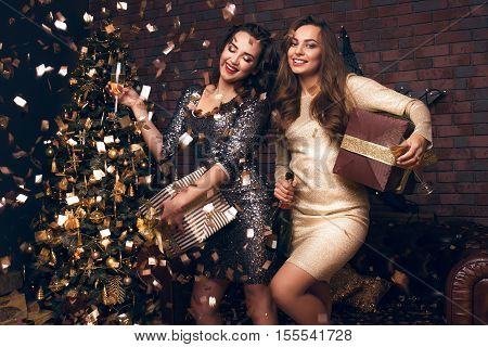 Happy New Year To You! Two Beautiful Young Women In A Confetti Celebration Christmas With A Presents