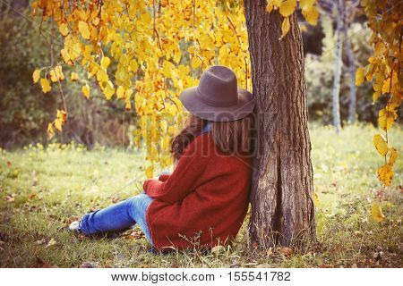 Beautiful young woman sitting in a autumn park