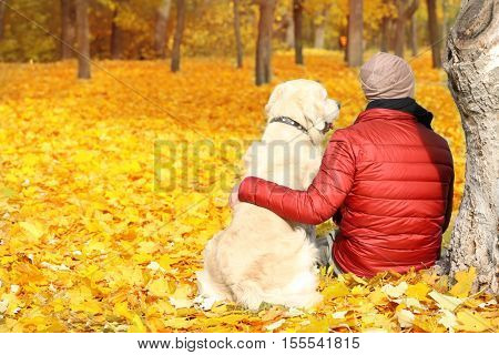 Man with his dog sitting under tree in beautiful autumn park