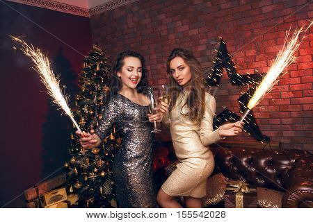 Two Beautiful Girls With A Fireworks In Their Hands Dancing On The Club, Fun And Waiting For Christm
