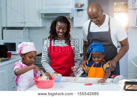 Family preparing cake in kitchen