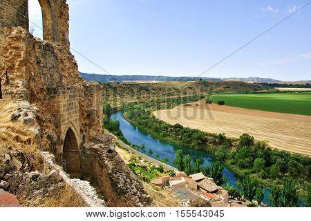 Paisaje natural con castillo viejo, río y campo