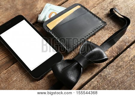 Leather wallet and other man accessories on wooden background