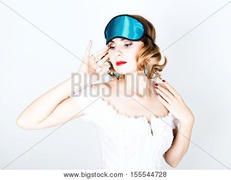 beautiful young woman in a pink dress and points for sleep, standing and posing. sleeping eye covering mask.