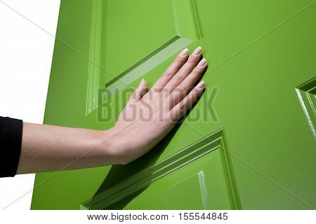 Woman pushes a green door open with her hand