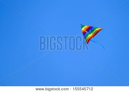 Colorful kite flying on background blue sky.