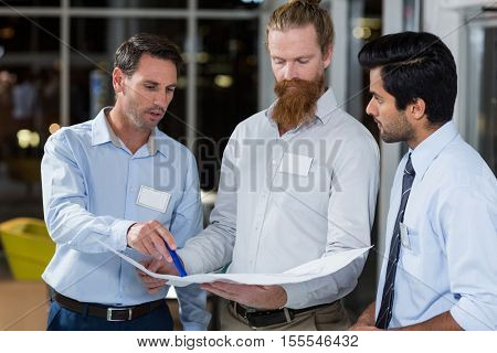 Businessmen discussing over blueprint in the office