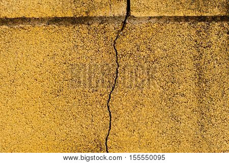 Surface of a yellow wall cracked by the passage of time
